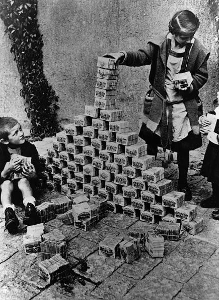 Children playing with bricks of fast worthless currency banknotes.