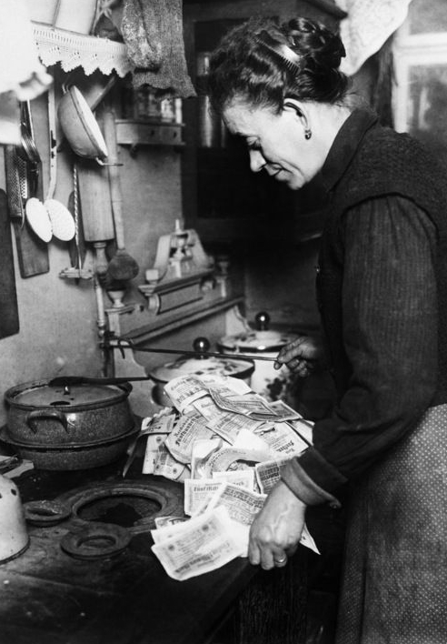 A German lady uses bundles of banknotes to fuel her stove.